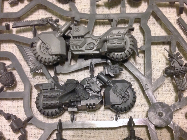 The top bike is from an old Space Marine Battlelion set.  The Ravenwing bike has crisper edges and smoother surfaces.  The detail, however, isn't much different.